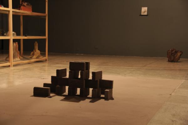 """Leonardo Amador, """"Sin título"""", instalación en ceniza, 2014. Atrás: Lisseth Balcazar, """"Sin título (Prueba de Artista. De la serie Ahí), grafito y carboncillo sobre papel"""", 2013; Iván Tovar, """"Todos los fuegos el fuego (fragmento)"""", escultura de arcilla, 2014."""